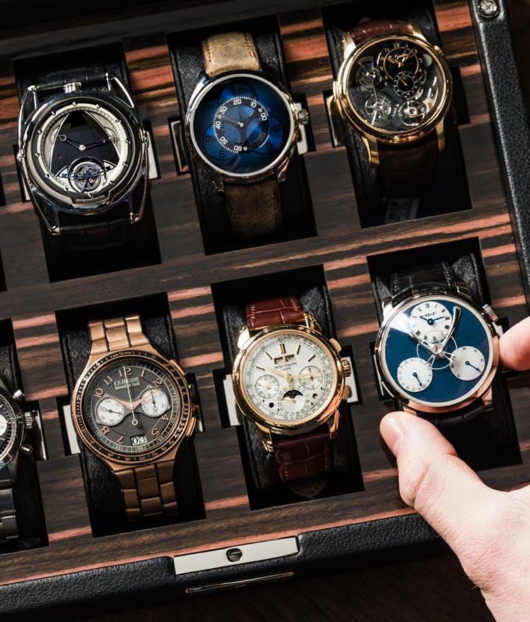 person choosing watch from a box of watches